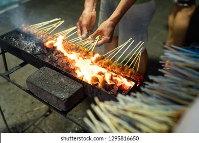 portrait of a seller cooking a skewers chicken meat with a grill, it is indonesian streetfood