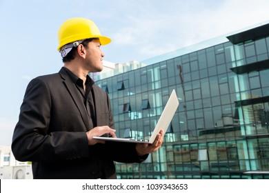 Portrait of senior architect using laptop against building background