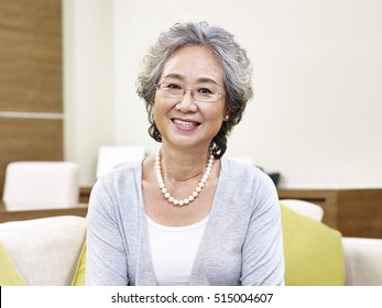 portrait of a senior asian woman, looking at camera smiling