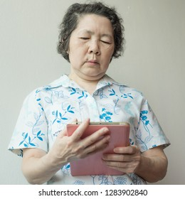 portrait of senior asian woman using smartphone and tablet