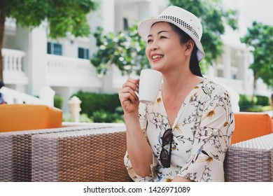 portrait senior asian woman wear a hat with a white cup of coffee in lobby of clubhouse