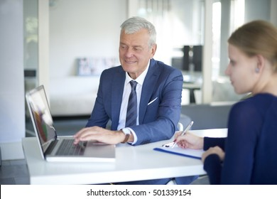 Portrait of senior banking advisor sitting in front of laptop and helping a client with her banking accounts.