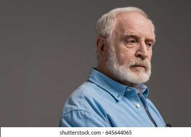 portrait of senior bearded man isolated on grey in studio