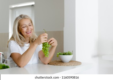 Portrait of senior beautiful smilling woman eating white grape in kitchen.