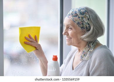 Portrait of senior beautiful woman posing and cleaning window at home