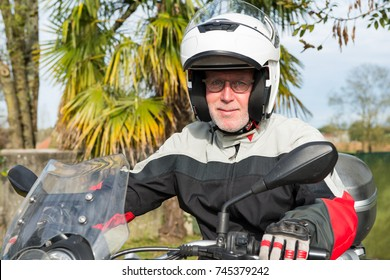 a portrait of a senior biker on his motorcycle