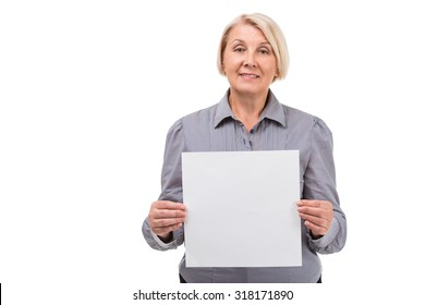 Portrait of senior blonde woman standing isolated on white background. Woman wearing grey blouse. Woman looking at camera and holding square sheet of paper