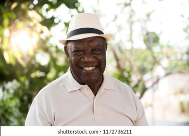 portrait of senior brazilian black man with white hat looking at camera spot in sunset and smiling. Horizontal shape, copy space.