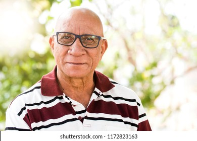 portrait of senior brazilian black man with glasses looking at camera in sunset and smiling. Horizontal shape, copy space