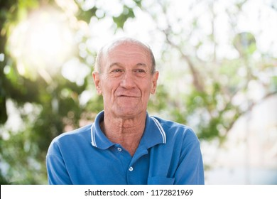 portrait of senior brazilian man looking at one spot in sunset and smiling. Horizontal shape, copy space