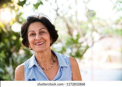 portrait of senior brazilian woman looking at camera in sunset and smiling. Horizontal shape, copy space