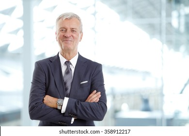 Portrait of senior broker standing with arms crossed while looking at camera and smiling.