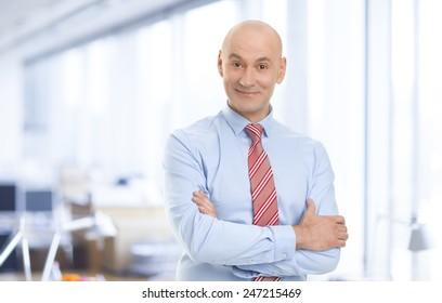 Portrait of senior broker standing at stock exchange.