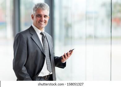 portrait of senior business executive using tablet pc