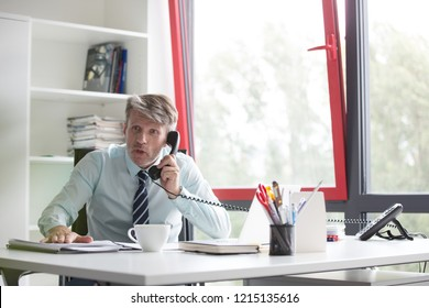 Portrait of a senior business man working in his office, he is making a telephone call he looks shocked and his slamming his hand on his desk