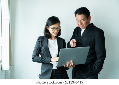 Portrait of a senior business man and a young business woman holding a laptop computer were discussing jobs