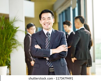 portrait of a senior business manager arms crossed looking at camera with a big smile.