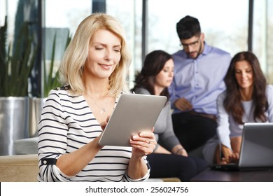 Portrait of senior business woman holding digital tablet while sitting at meeting. Business people.