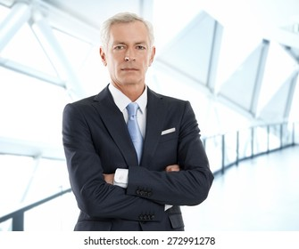 Portrait of senior businessman with arms crossed standing at office while looking at camera.