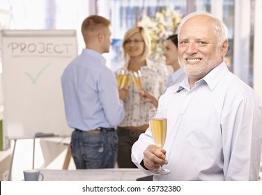 Portrait of senior businessman celebrating project done in office with champagne, employees talking in background.?