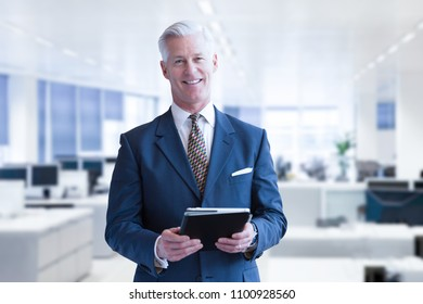 Portrait of senior businessman in front of his modern office with tablet