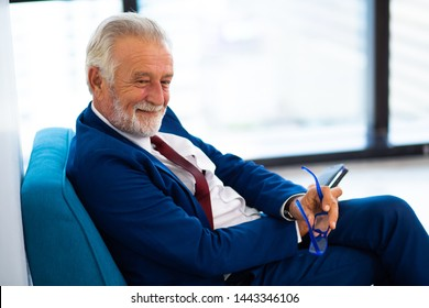 Portrait of senior businessman in front of his modern office. Portrait of a handsome CEO smiling