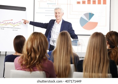 Portrait of a senior businessman gesturing while giving a presentation at a business conference.
