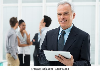 Portrait Of Senior Businessman Holding Digital Tablet at Office