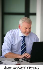 Portrait of a senior businessman with a laptop computer