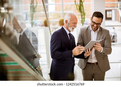 Portrait of senior businessman pointing and showing something to junior partner on digital  tablet at office