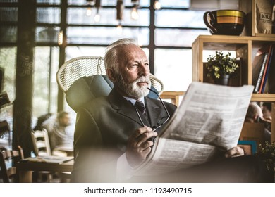 Portrait of senior businessman sitting at his office, ridding newspapers.