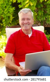Portrait of senior businessman sitting at home in the garden and working on laptop.