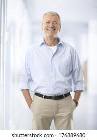 Portrait of senior businessman standing against white background.