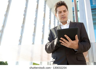 Portrait of a senior businessman standing by a modern architecture glass office building in the city, using a digital technology tablet pad.