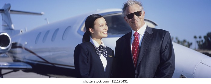Portrait of senior businessman standing with stewardess in front of an aircraft