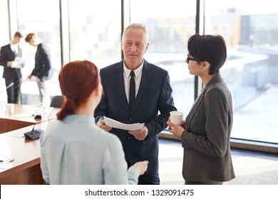 Portrait of senior businessman talking to employees after business meeting in office, copy space