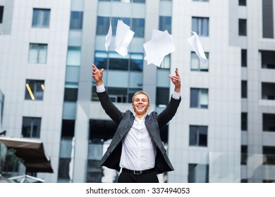 Portrait of senior businessman throwing sheets of paper into the air