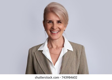 portrait of a senior businesswoman smiling. Isolated on grey background