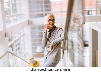 Portrait of senior businesswoman using mobile phone in modern ofice