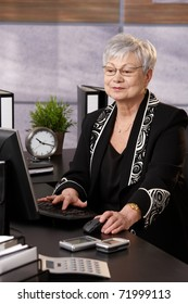 Portrait of senior businesswoman working with computer at desk in office.?