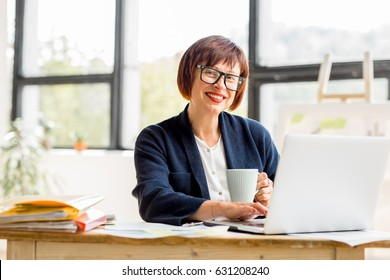 Portrait of a senior businesswoman working with documents and laptop at the bright modern office interior
