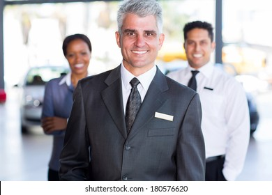 portrait of senior car dealership principal with staff on background