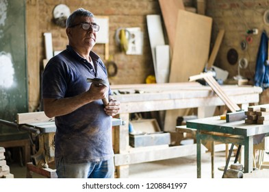 Portrait of senior carpenter. Standing with the background of your carpentry behind