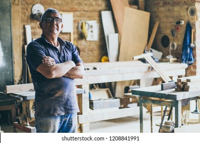 Portrait of senior carpenter. Standing in his workshop and looking at camera.