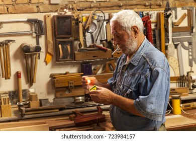 Portrait of senior carpenter.He standing in his workshop and lighting a cigarette.