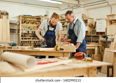 Portrait of senior carpenter teaching apprentice  while working  in joinery workshop, copy space
