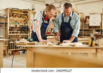 Portrait of senior carpenter teaching apprentice  standing at table in workshop, copy space