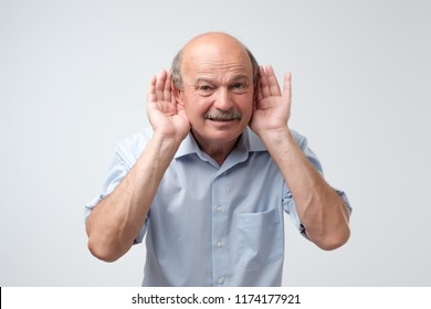 Portrait of senior casual man which overhears conversation over white background. Speak loudly please concept. What did you say