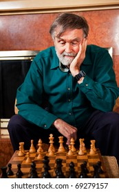 A portrait of a senior caucasian man playing chess