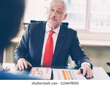 Portrait of senior Caucasian manager sitting at table and listening to client or partner with raised eyebrows. Meeting and relationship management concept